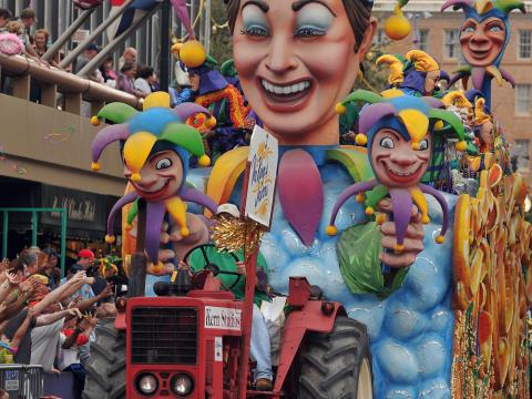 A colorful Mardi Gras float parades through the street