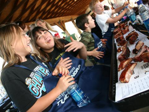 Kids enjoying ribs during the WhistleStop Bar-B-Que Weekend in Huntsville, Alabama
