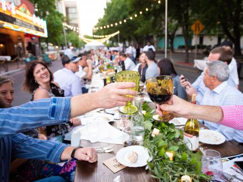 Cena en Main Street de Stockton en una larga mesa al aire libre durante el evento Feast at the Fox, con preparaciones de la granja a la mesa